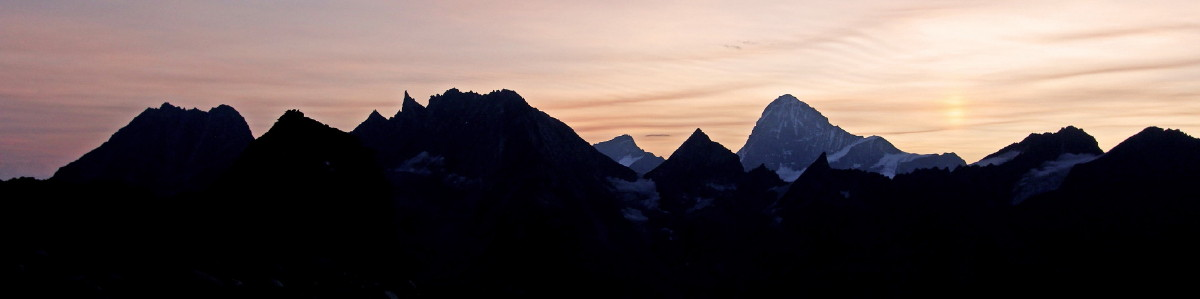 Photo of Dawn light over the Dent Blanche. The Aiguille de la Tsa range east of Arolla silhouetted in the foreground.
