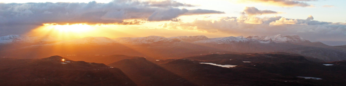 Photo of rays of sun light streaming down on to the hills west of Strath More seen from near the summit of Ben Hope. Arkle and Foinaven are in the right (northern) half of the photo