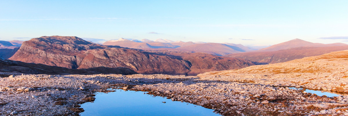 Photo of an evening view over the Kinlochewe valley from the northern slopes of Beinn Eighe to Beinn a' Mhuinidh (left), the Fannich hills (centre) and Fionn Bheinn (right)