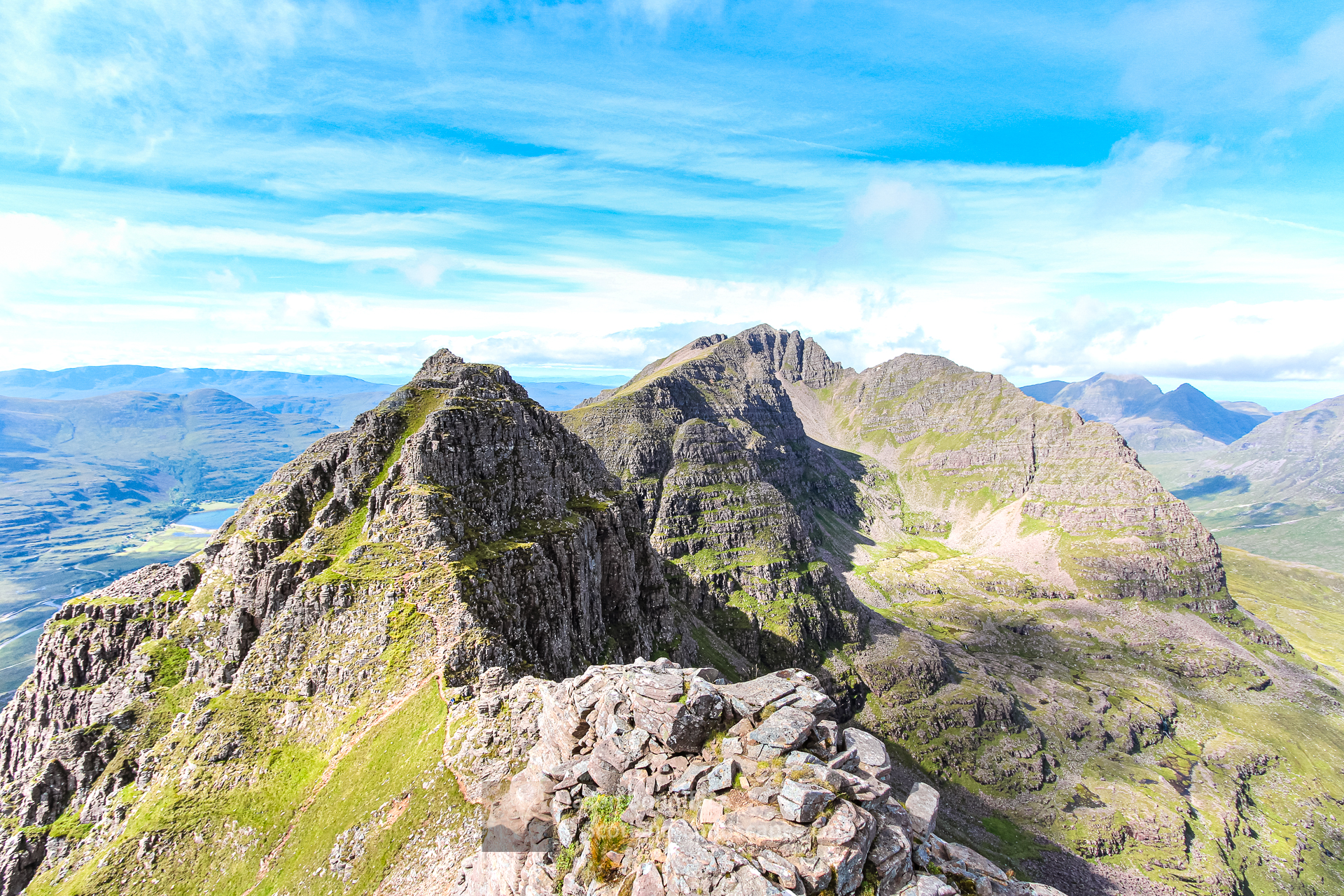Photo of summer on the Am Fasarinen Pinnacles of Liathach; the second Munro of the mountain, Mullach an Rathain, in the distance