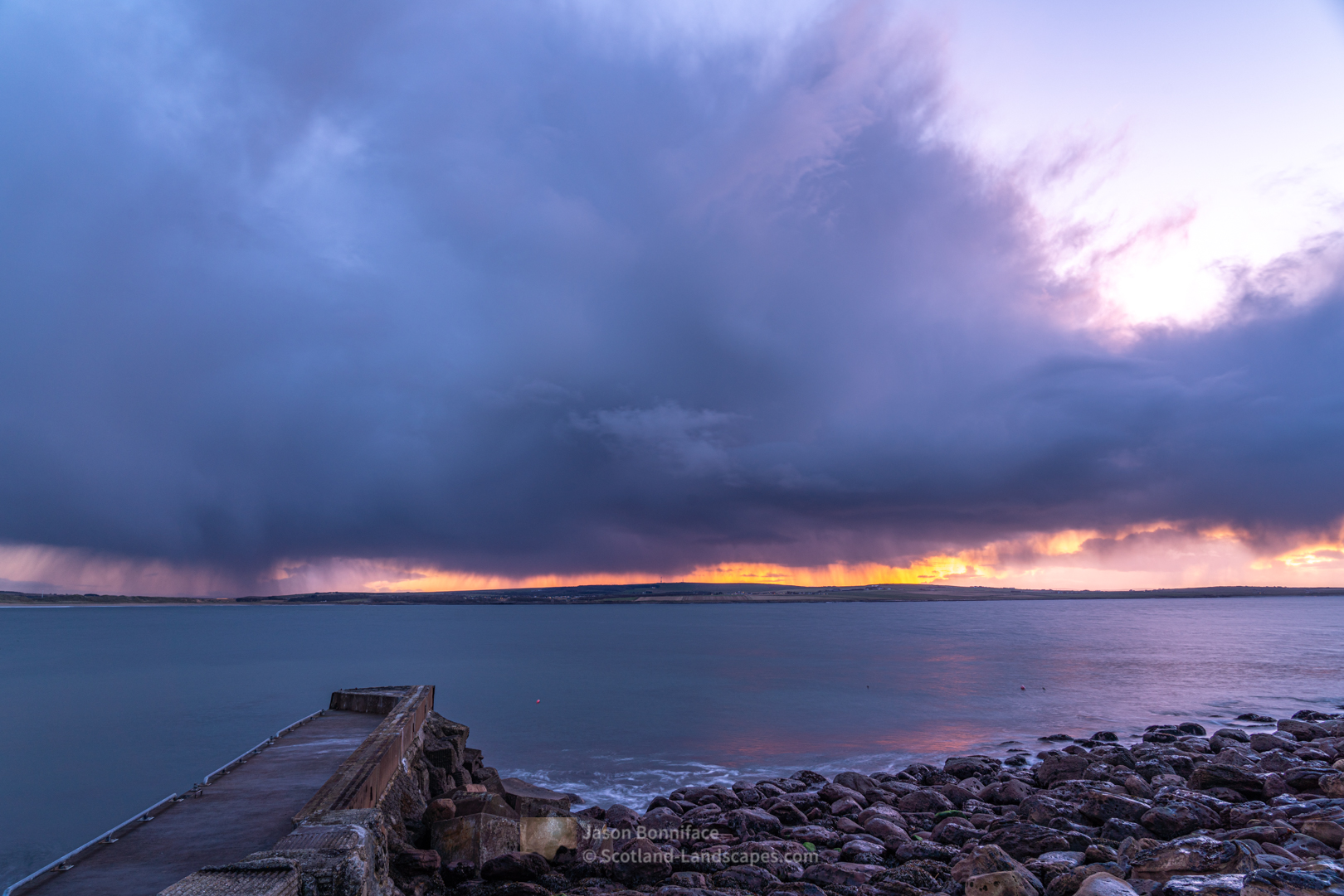 The sunset afterglow lighting the horizon beneath a huge shower cloud moving in from the north