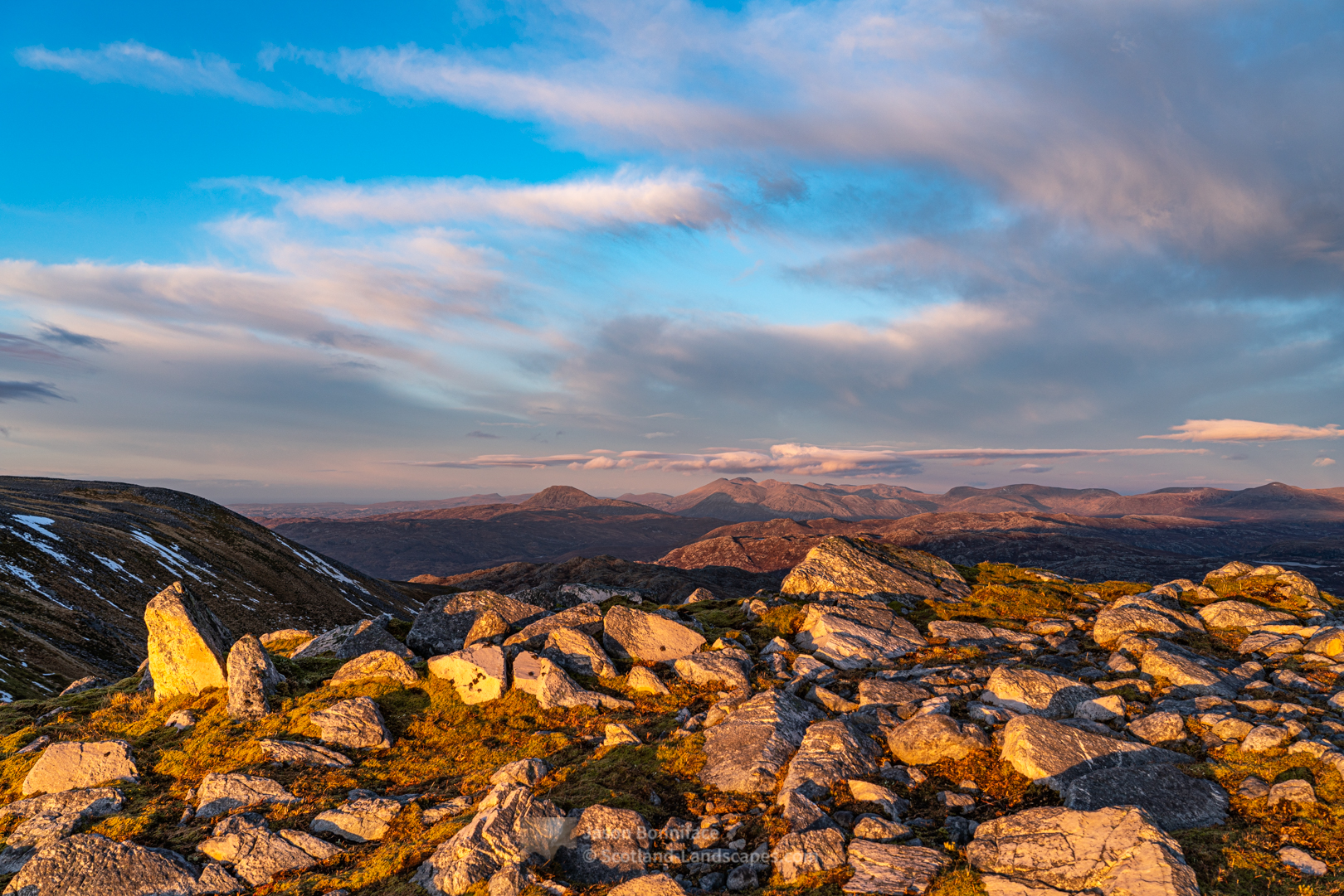 Sunlit rocks on Glas Bheinn with Ben Stack, Arkle and Foinaven beyond